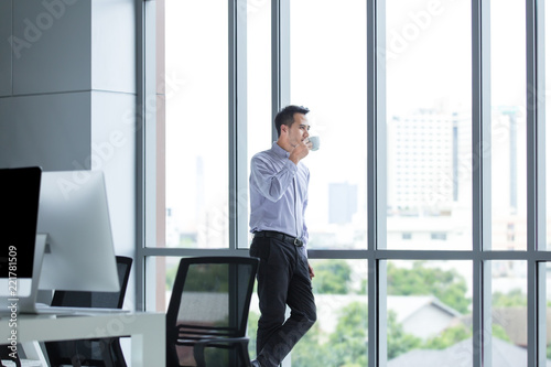 Fototapeta Young Asian businessman standing against window relaxed in his hands is cup of coffee look ahead.