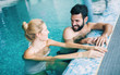 Leinwanddruck Bild - Happy attractive couple relaxing in swimming pool