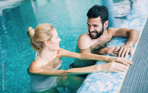 Leinwanddruck Bild Happy attractive couple relaxing in swimming pool