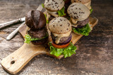 Homemade tasty grilled burgers with beef, tomatoes, cheese, sweet onions and a green salad on a wooden background - 221783595