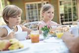 Kids having breakfast outside the house - 221784152