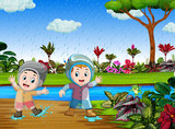 the happy children play with the water in the rainy season 