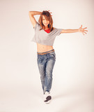 Young beautiful woman girl in red pants and plaid shirt dancing hip hop on a gray light background - 221788723
