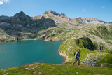 man hiker climbing a slope, Lake Estaens in the background
