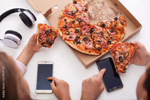 Young teenagers checking their phones while eating pizza - top view of the table - 221809748