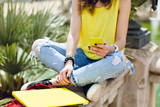 Yellow laptop, phone in hand of a girl in yellow T-shirt and jeans  sitting on fence in summer park. - 221813987