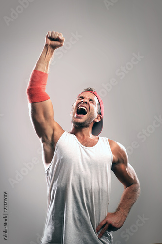Fototapeta Athlete with a raised hand celebrates victory