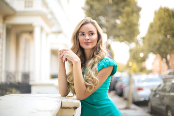 Beautiful elegant woman standing in the street, looking around