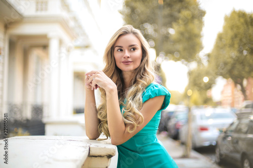Beautiful elegant woman standing in the street, looking around - 221815581