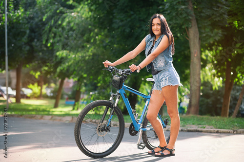 Young pretty brunette girl in denim shorts with a bicycle on the street in summer.
