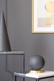 Black ball and cone on table against grey wall with poster in museum interior. Real photo - 221825587