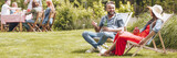 Horizontal photo of two friends talking and sitting on sunbeds in a garden - 221825754