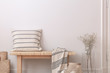 Pillow and blanket on wooden bench next to flowers in beige minimal flat interior. Real photo