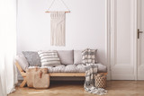 Beige wooden sofa and bags in white loft interior with decor on the wall next to door. Real photo - 221825904