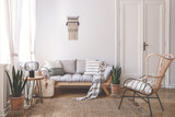 Armchair near beige sofa with pillows in living room interior with plants and door. Real photo - 221825945