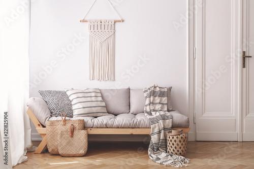 Beżowa drewniana sofa i torby w białym poddaszu wnętrze z wystrojem na ścianie obok drzwi. Prawdziwe zdjęcie