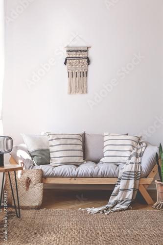 Koc i poduszki na drewnianej kanapie w beżowym pokoju dziennym z brązowym dywanem. Prawdziwe zdjęcie