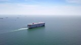 Aerial view of logistics concept cargo ship sailing out to the open sea leaving Laem Chabang dockyard in Chonburi Province, Thailand - 221827749