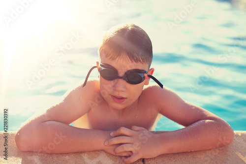 Boy holding swimming pools edge outdoors in sunset