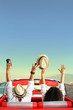 Young couple in retro car with hands up, vacation and happiness