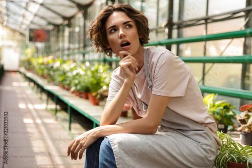 Leinwanddruck Bild Young woman gardener sitting over flowers plants in greenhouse.