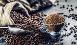 Granules of instant coffee in glass cup and coffee beans.