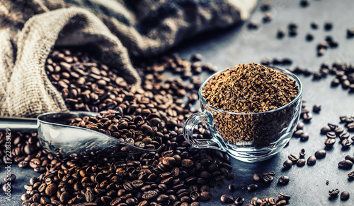 Granules of instant coffee in glass cup and coffee beans. - 221835129