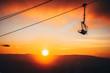 Ski lift silhouette in ski resort, winter sunset in background.