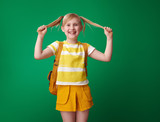 happy pupil with backpack with tails against green background - 221840126