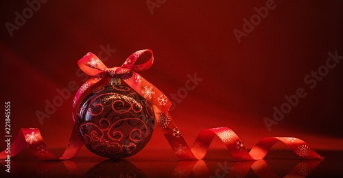 Red Christmas Ball with Ribbon and Bow on Red Background With Reflection