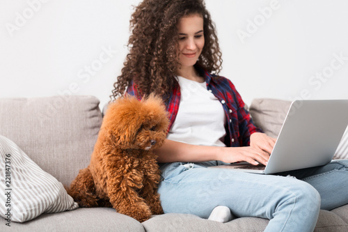 Woman working at home with cute dog - 221847376