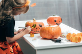 side view of cute child painting pumpkins for halloween at home - 221848158