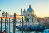 Beautiful view of traditional Gondolas on Canal Grande with historic Basilica di Santa Maria della Salute in Venice, Italy
