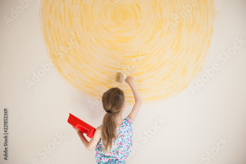 thin little talented girl drawing art work yellow sun on wall with brush