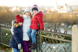 Young mother and her two daughters having fun on beautiful winter day in Vilnius. - 221855509