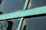 Old window with unwashed windowpane and chapped window frame painted green - 221865348