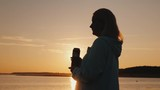 Woman drinks beer from a can on the lake. Standing alone, looking at the sunset - 221865529