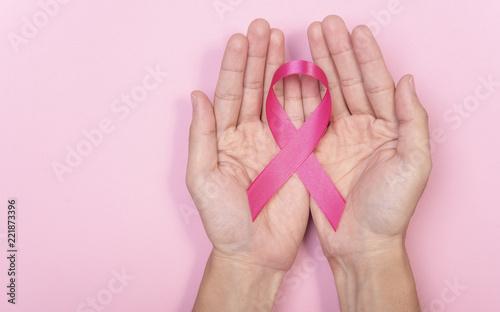 kobiety ręka trzyma różową tasiemkową raka piersi na różowym tle. z kopią miejsca