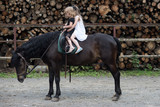 Children sit in rider saddle on animal back - 221873773