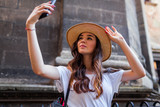 Young tourist woman taking selfie using smartphone. Stylish traveler girl walking on old city street - 221878316