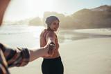 Young couple walking along the beach - 221889310
