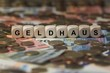 Leinwanddruck Bild - Geldhaus - Holzwürfel mit Buchstaben bedruckt im Hintergrund liegen Banknote und Kleingeld