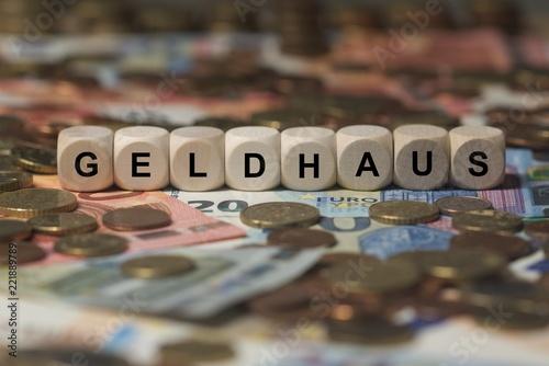 Leinwanddruck Bild Geldhaus - Holzwürfel mit Buchstaben bedruckt im Hintergrund liegen Banknote und Kleingeld