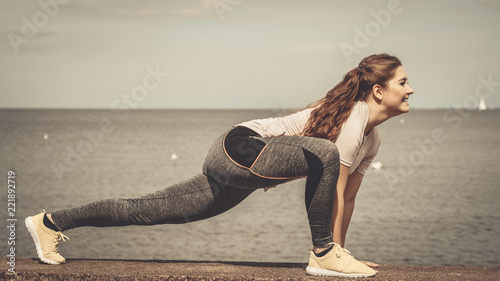 Poster Woman stretching legs next to sea