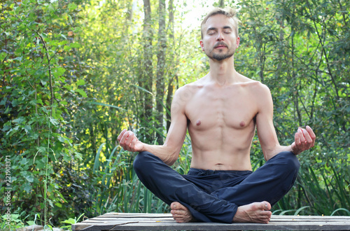 Poster Young bearded man practicing yoga outdoor. His sitting in pose of lotus with their eyes closed and meditating. Green forest on background