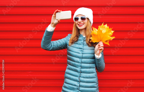 Fashion autumn smiling woman takes a picture self portrait on a smartphone with yellow maple leaves over colorful red background - 221909784