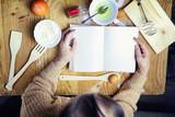 Open recipe book in the hands of an elderly woman - 221915591
