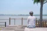 公園で座って海を眺めるシニア女性の後ろ姿 - 221919153