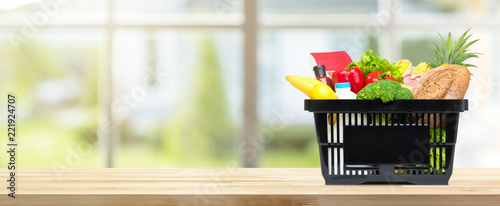 Food and groceries in shopping basket on kitchen table banner background