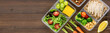Leinwandbild Motiv Healthy ready to eat food in meal boxes on wood banner background